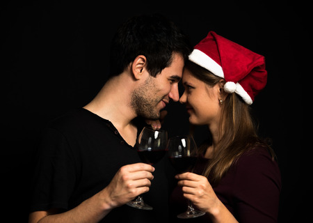 touching noses: Young Christmas couple, wearing red hut, holding wine glasses, on black background, touching noses Stock Photo