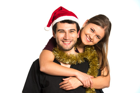 lovers: young couple, man and woman, smiling, happy, wearing Christmas decoration, hugging