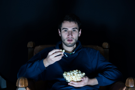 scarry: young man sitting in the dark room in the front of tv watching movie and eating popcorn