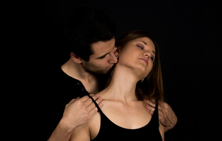 adult nude: Young couple, man and woman on the black background kissing Stock Photo