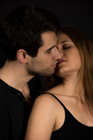 nude girl pretty young: Young couple, man and woman on the black background kissing Stock Photo