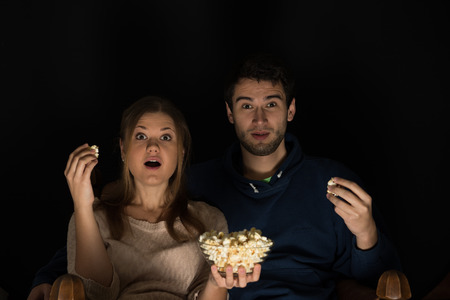 Young couple, man and woman, sitting in the dark room in the front of tv watching movie and eating popcorn, showing emotions