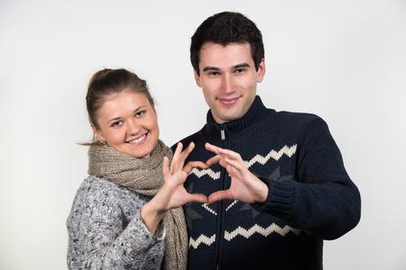 amigos abrazandose: retratos de la joven pareja en el amor, hombre y mujer, vistiendo ropa de invierno, mostrando un signo de amor Foto de archivo