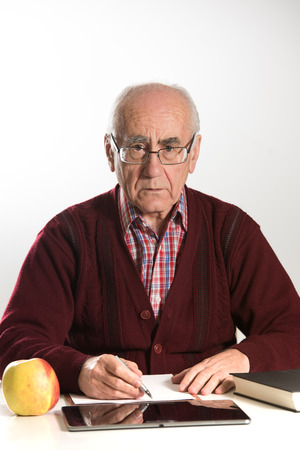 old seniour man wearing eyeglasses, working with documents, using pen, book and tablet pc looking serious wearing red sweater Stock Photo