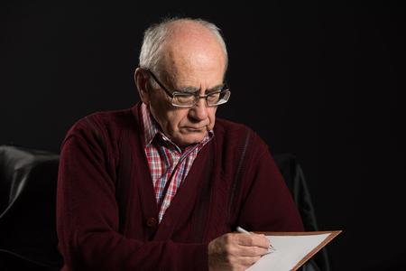 hombre escribiendo: El viejo hombre que llevaba lentes que escribe algunos avisos con la cacerola y papel blanco Foto de archivo
