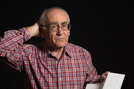 scrooge: elderly man, wearing checked shirt reads bank document, final notice
