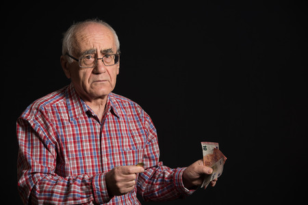 scrooge: old man wearing checked shirt and eyeglasses holding euro banknotes