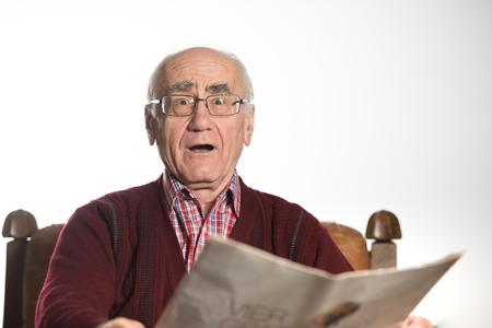wondering: old seniour man wearing eyeglasses, reading newspapper, wondering wearing red sweater