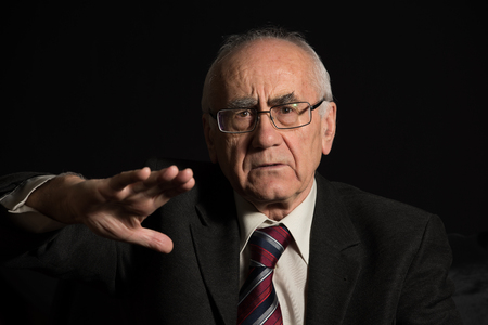 older businessman, wearing eyeglasses on black background discussing and articulates with his hand