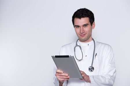 bata blanca: young doctor, male in white coat, with stethoscope working with tablet pc
