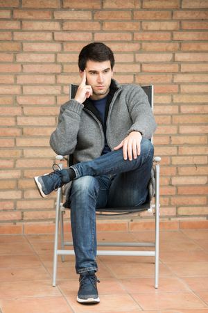 fantasize: young man sitting in chair in front of bricks wall Stock Photo