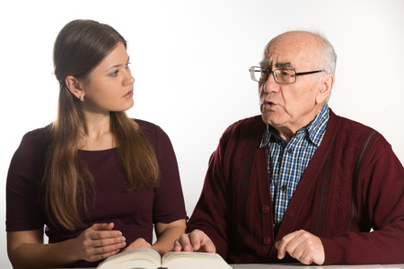 dementia: young woman helping senior man to pronounce sound and read book, man has dementia Stock Photo