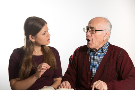 pronounce: young woman helping senior man to pronounce sound and read book, man has dementia Stock Photo