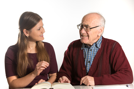 young woman helping senior man to pronounce sound and read book, man has dementia Banco de Imagens