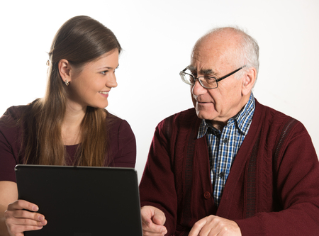 young woman helping senior man to work with tablet computer and fill some paper documents