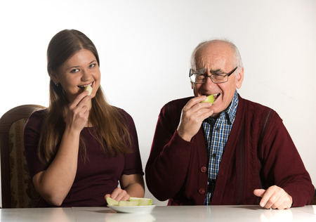senior eating: young woman and senior man eat green apple