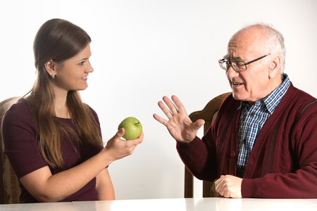 renounce: young woman helps senior man to eat green apple