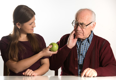 old age home: young woman helps senior man to eat green apple