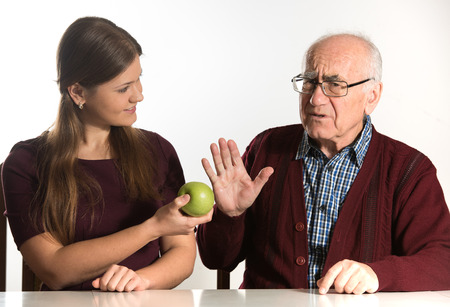 disinclination: young woman helps senior man to eat green apple