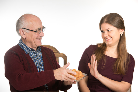 disinclination: old senior man and young woman eating potato  chips