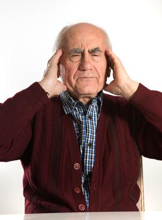 oldness: old senior man having problems, thinking, beeing serious, having headache