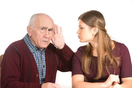 decrepitude: young woman makes hearing test for old senior man Stock Photo