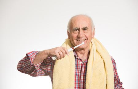 old senior man brushing his teeth