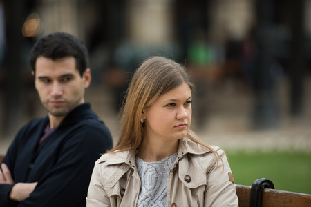 two women hugging: young couple having love fight on the bench in park in Paris, France Stock Photo