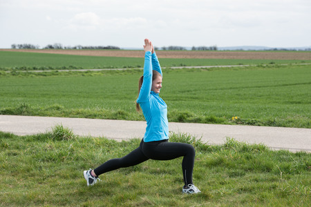 20 years old: 20 years old woman stretching (doing sport) outdoors