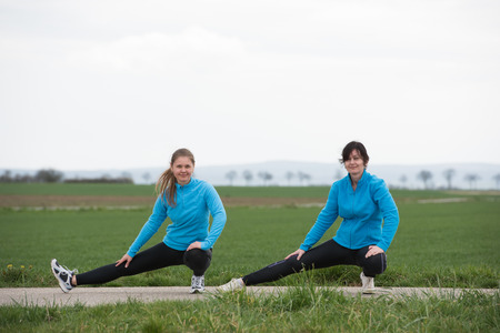20 years old: two women, 20 and 40  years old  stretching (doing sport) outdoors