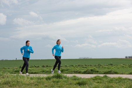 20 years old: two women, 40 and 20 years old, jogging (running) outdoors Stock Photo
