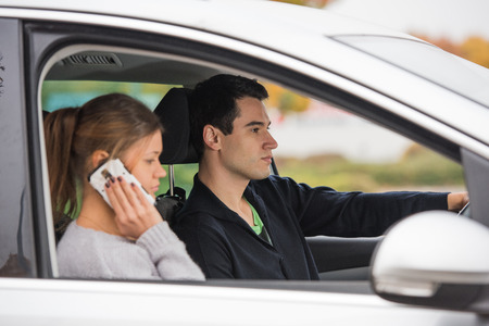 loaning: young couple, man and woman, in silver car, man in driving, woman talks on the smartphone