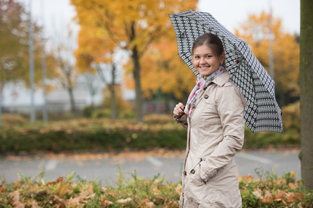 Young woman standing under umbrella in autumn park, wearing beige mackintosh