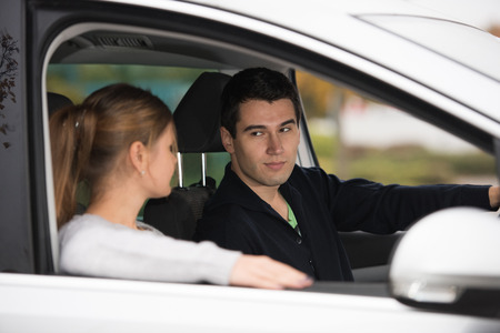loaning: young couple, man and woman, in silver car, man in driving, focus on wan