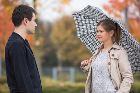 mackintosh: Young couple in autumn park, woman standing under umbrella, wearing beige mackintosh