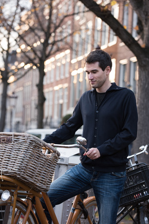 cycler: young man in Amsterdam on bicycle with basket