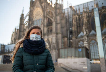 portrait of young german woman in front of Cologne Cathedral (Kölner Dome), Germany, wearing medical mask againg coronavirus (COVID-19) fighting agaings pandemic