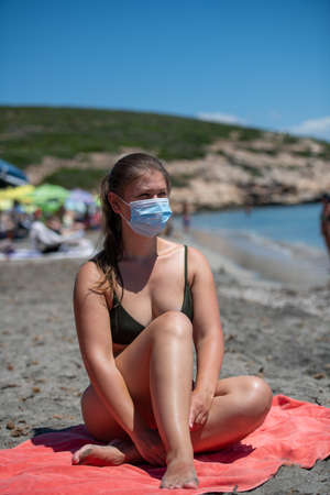 A young woman having a rest on the beach wearing a protective face mask because of COVID-19