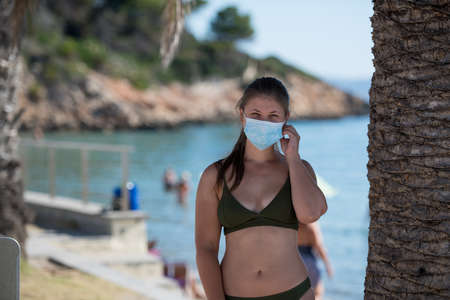 A young woman at a beach, wearing a protective face mask because of COVID-19 Banco de Imagens