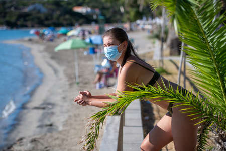 Young woman relaxing at the beach with a face mask protection and practicing social distancing Banco de Imagens