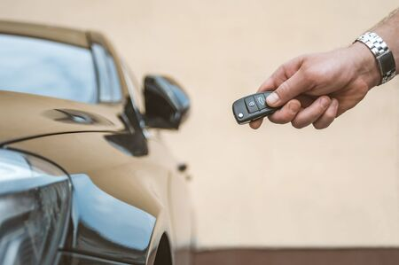 A man opens the car with a keychain, in the background is a yellow wall Reklamní fotografie