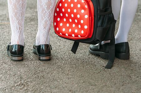 Legs of girls in school uniform with a backpack on the background of asphalt. Back to school concept
