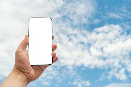 Mock Up smartphone on the background a blue sky with clouds. Concept on the topic of Technology