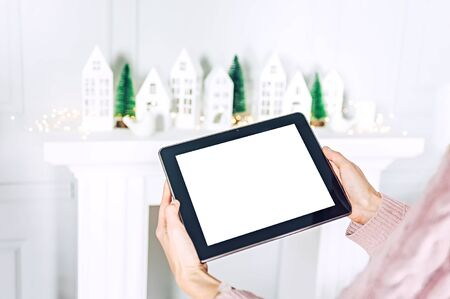 Mock up of the tablet in the hands of the girl on the background, christmas tree with decorative houses festive decoration