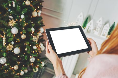 Mock up tablet in the hands of a girl on the background, New Year Christmas tree with holiday decoration