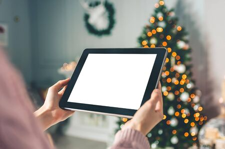 Mock up black tablet in the hands of a girl on the background, New Year Christmas tree with holiday decoration Stockfoto