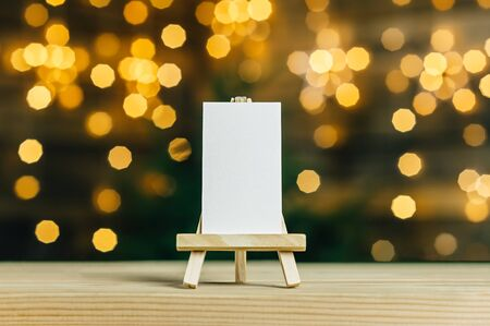 Mock Up mini easel with a white business card. Against the backdrop of a bokeh of stars garland Archivio Fotografico