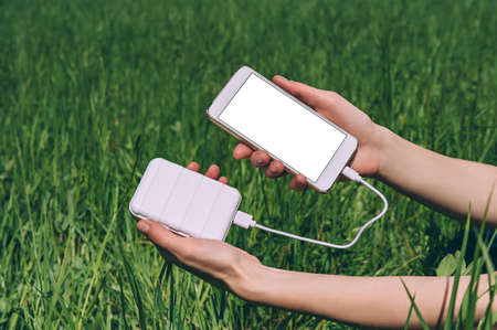 Mock-up of a smartphone and a Power Bank in the girl's hand. against the background of a field with green grass Stock fotó