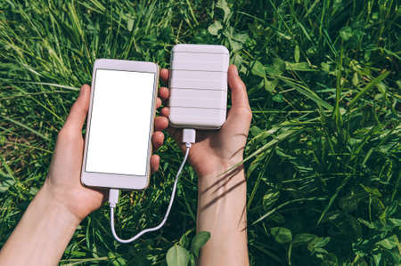 mock-up of a smartphone in the hands of a girl with a charge from a power bank. against the background of a green field