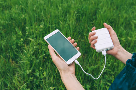 close-up of charging the phone from the power bank in the hands of the girl. against the backdrop of nature Stock fotó